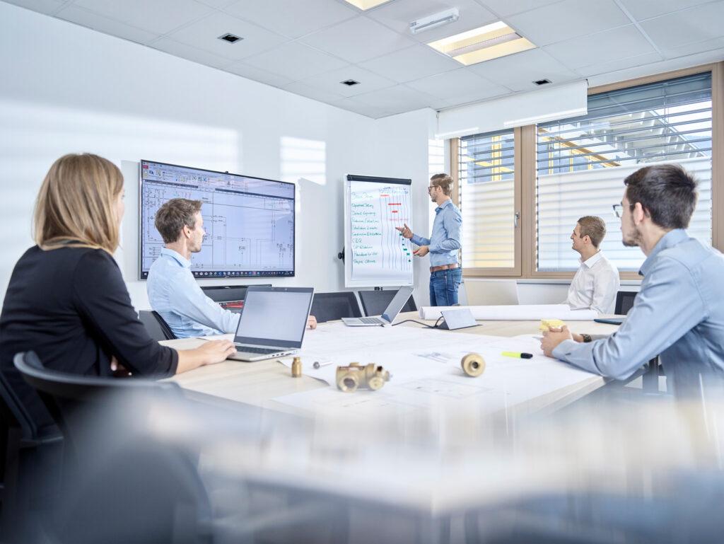 Fünf Mitarbeiter besprechen Projekt in Besprechungsraum, ein Mitarbeiter präsentiert