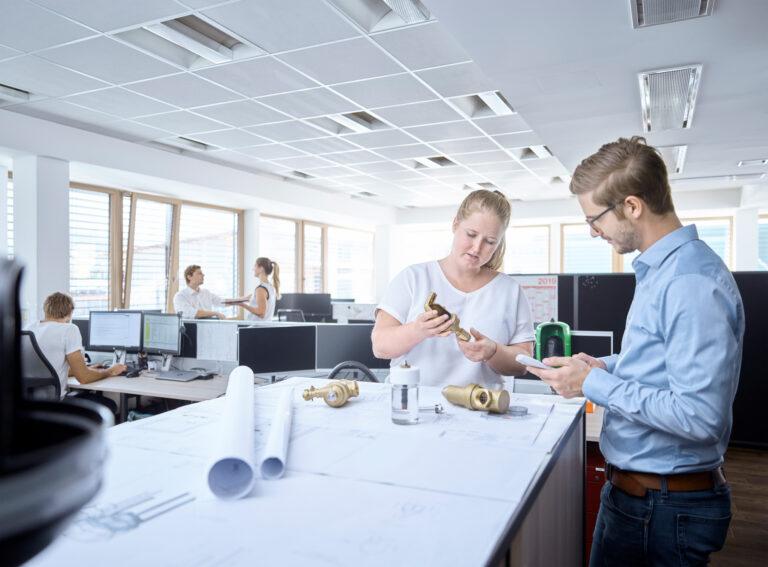 Mitarbeiterin zeigt und erklärt einem zweiten Kollegen ein Ventil im Büro
